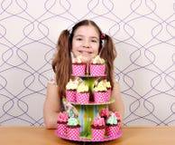 小女孩用在桌上的甜松饼 免版税库存图片