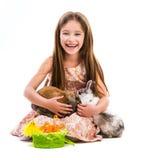 小女孩用她的两只兔子 免版税库存图片