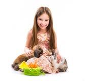小女孩用她的两只兔子 免版税图库摄影