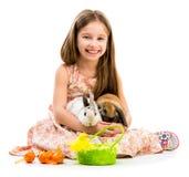 小女孩用她的两只兔子 免版税库存照片