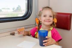 小女孩用愉快的面孔饮料茶用在火车的三明治在船外第二等的支架的桌上 库存照片