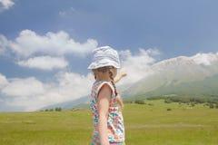小女孩用意大利语指向山土坎视图的阿布鲁佐地区亚平宁山脉 免版税库存照片