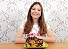 小女孩用新月形面包早餐 免版税库存图片