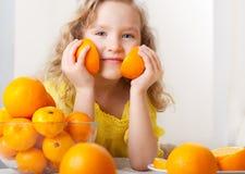 小女孩用桔子 免版税库存图片