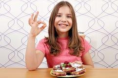 小女孩用樱桃饼和好手签字 库存照片