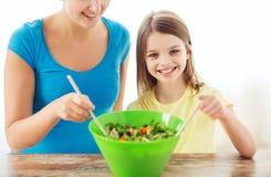 小女孩用母亲混合的沙拉在厨房里 免版税图库摄影