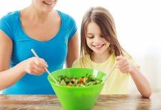 小女孩用母亲混合的沙拉在厨房里 库存照片