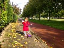 小女孩用滑行车挥动的手和微笑 免版税库存图片