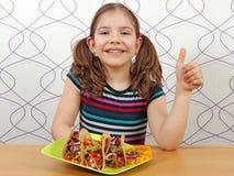 小女孩用炸玉米饼和赞许 免版税库存图片