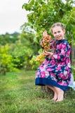 小女孩用葡萄在庭院里 库存图片