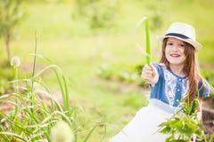 小女孩用葱 免版税库存图片