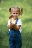 小女孩用蘑菇在手中在绿色草坪 库存照片