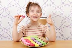 小女孩用蛋白杏仁饼干和赞许 库存图片