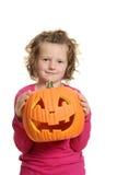 小女孩用被雕刻的万圣夜南瓜 免版税库存图片