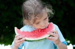 小女孩用西瓜 免版税库存图片