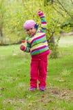 小女孩用他的手提高了吃棒棒糖户外 免版税库存照片
