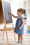 小女孩画与在黑板的白垩 免版税图库摄影