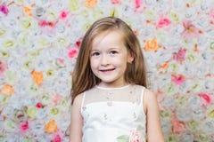 小女孩画象花卉背景的 库存图片