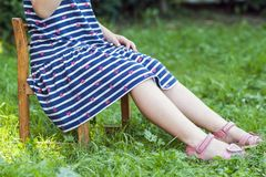 小女孩的腿和脚礼服的坐在gree的一把椅子 库存照片