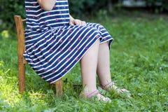 小女孩的腿和脚礼服的坐在gree的一把椅子 库存图片