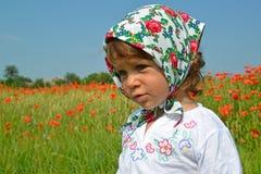 小女孩的画象一块五颜六色的方巾的反对红色鸦片 库存图片