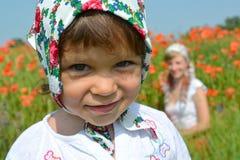 小女孩的画象一块五颜六色的方巾的反对红色ppoppies 免版税库存图片