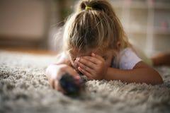 小女孩盖了眼睛,当看电视时 免版税图库摄影
