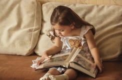 小女孩看一个家庭册页 库存图片