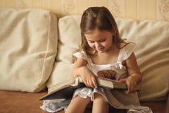 小女孩看一个家庭册页 库存照片