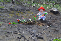 小女孩种植在被烧的地面的郁金香 免版税图库摄影