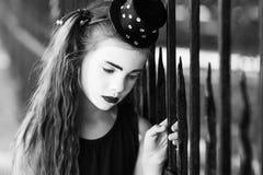小女孩笑剧是哀伤的身分在篱芭 免版税库存图片