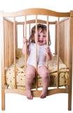 小女孩笑的坐在床上 库存照片