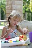 小女孩绘一个南瓜 免版税库存照片