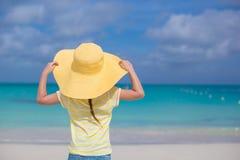 小女孩背面图一个大黄色草帽的在白色沙子海滩 免版税库存图片