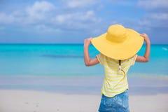 小女孩背面图一个大黄色草帽的 免版税图库摄影
