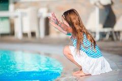 小女孩获得与飞溅的乐趣在游泳池附近 免版税库存图片