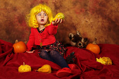 小女孩获得乐趣为万圣夜用南瓜和帽子 免版税库存照片