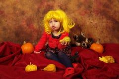 小女孩获得乐趣为万圣夜用南瓜和帽子 免版税库存图片