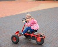 小女孩获得驾驶脚蹬汽车的乐趣在天 免版税库存照片