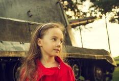 小女孩葡萄酒画象在军事坦克附近的 免版税库存图片
