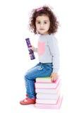 小女孩蓝色牛仔裤坐堆书 免版税库存图片