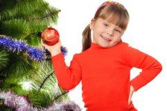小女孩装饰一个毛皮结构树。 免版税库存照片