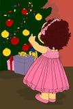 小女孩装饰了圣诞树 免版税图库摄影
