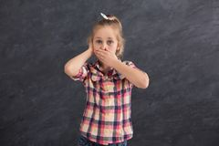 小女孩覆盖物嘴和耳朵用手 免版税库存图片