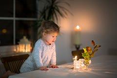 小女孩观看的蜡烛画象在暗室 库存图片