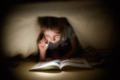 小女孩读一本书在有一个手电的一条毯子下在一个暗室在晚上 免版税库存照片