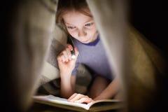 小女孩读一本书在有一个手电的一条毯子下在一个暗室在晚上 库存照片