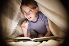 小女孩读一本书在有一个手电的一条毯子下在一个暗室在晚上 免版税库存图片