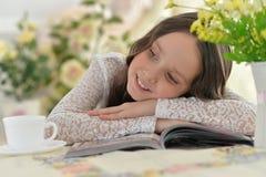 小女孩读书杂志 免版税库存照片