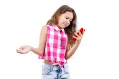 小女孩读在电话的sms和微笑着 免版税库存照片